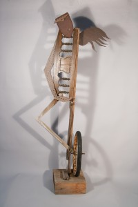 standing figure with wing and wheel, mixed-media sculpture